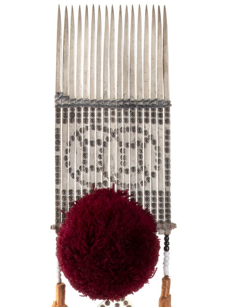 Miao Paktong hair comb is a precious decorative object realized in Tibet in the 1970s.  Engraved with two intertwined coins as symbols of good luck, this good fortune accessory is made of Paktong (an alloy of zinc, copper and nickel, resembling