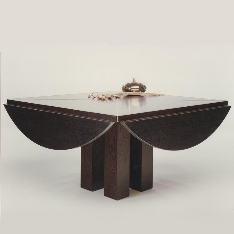 This elegant squared table is extendible and can be made in Italian walnut wood, American dark walnut, maple wood, cherry wood, durmast oak wood, or durmast oak with a wenge color. The solid wood adds elegance and warmth to this piece whose top