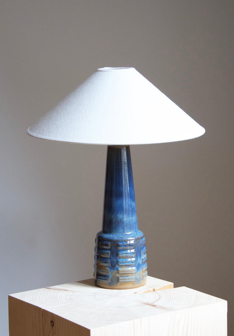 A table lamp produced by Michael Andersen Keramik. In stoneware. Marked. With production label  Stated dimensions exclude lampshade. Height includes socket. Sold without lampshade.  Other ceramicists of the period include Axel Salto, Arne Bang,