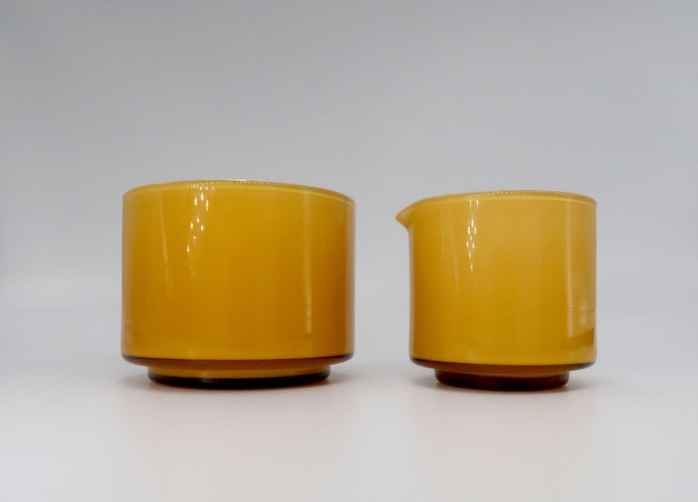Beautiful Danish Mid-Century Modern umber, warm caramel and milky white glass sugar bowl and creamer set. Designed by Michael Bang for Danish Holmegaard Glassworks manufactured in 1970. From the Palet series. In excellent condition.