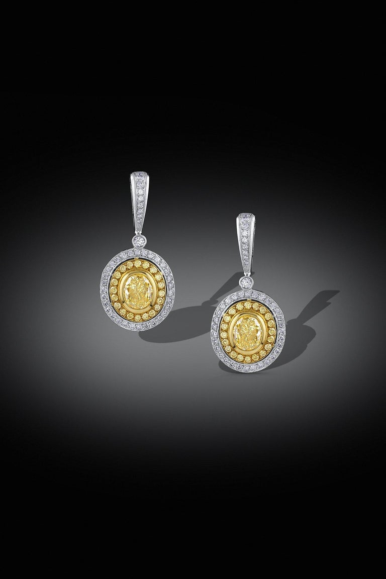 Earrings with perfectly matched 1.07ct and 1.06ct GIA certified fancy yellow oval cut diamonds. There are additional yellow and white diamonds in the 18k yellow and white gold settings. The total diamond weight is 3.05cttw.