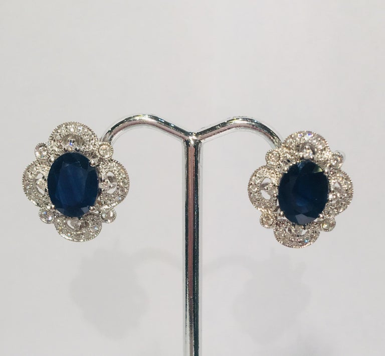 Elegant 14 karat white gold post earrings for pierced ears from noted Beverly Hills jeweler, Michael Christoff, feature a prong set, oval cut, dark blue sapphire surrounded by a sparkling filigree halo of bezel, prong and pave set diamonds, giving