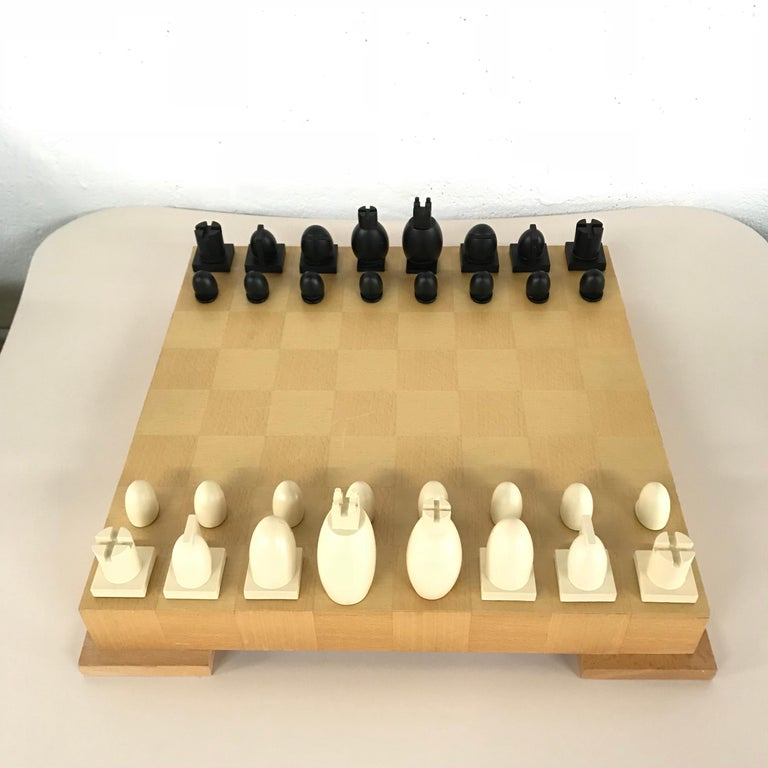 Postmodern chess and checkers set rendered in two-tone maple, with composite pieces, designed by Michael Graves, Memphis Group designer.  Two complete sets of Chess pieces and original instructions.