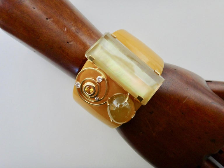 A Bakelite cuff forms the foundation for this one-of-a-kind cuff bracelet.  The composition consists of a large citrine masterfully cut by Jerry Newman, a golden Botswana agate, a yellow sapphire and white diamonds.  The golden cluster of gems are