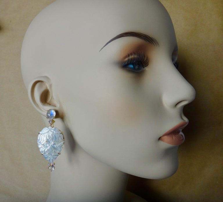 Sensational blue flash moonstones (origin: Sri Lanka) are paired with beautifully carved mother-of-pearl (origin: Indonesia) in these one-of-a-kind dangle earrings.  The blue flashes move throughout the cabochon moonstones.  The mother-of-pearl is