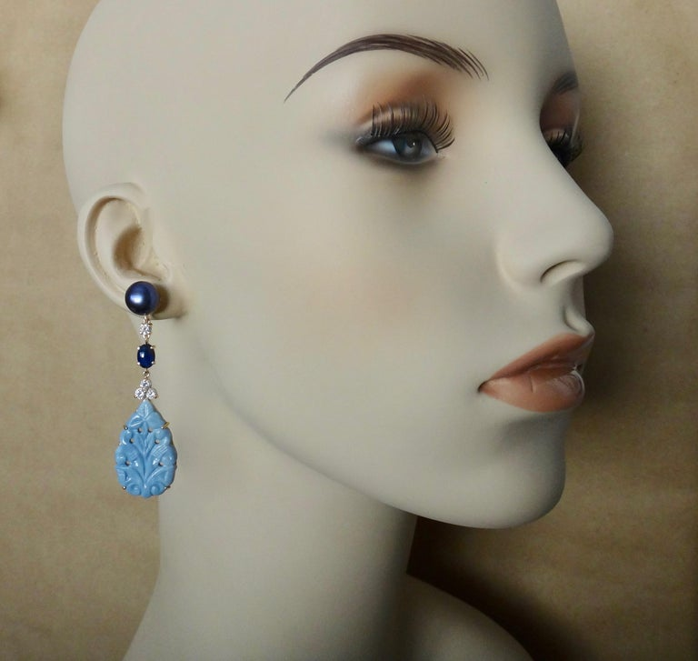 Beautifully carved blue opal (origin: Peru) pendants are featured in these one-of-a-kind dangle earrings.  The opals are complimented by cabochon blue sapphires (origin: Thailand), white diamonds and gem quality Tahitian blue/black pearls.  The 18k