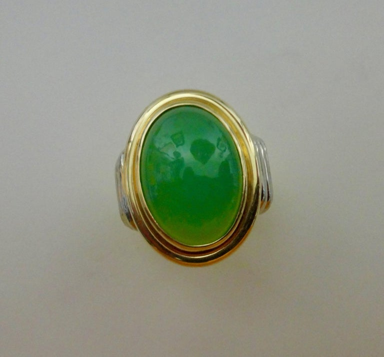 A gem quality chrysoprase (origin: Australia) is set in a hand fabricated 18k yellow and white gold ring.  The bezel set gem is a rich apple green and possesses a flawless finish.  The ribbed design of the shank keeps ware to a minimum.  The ring is