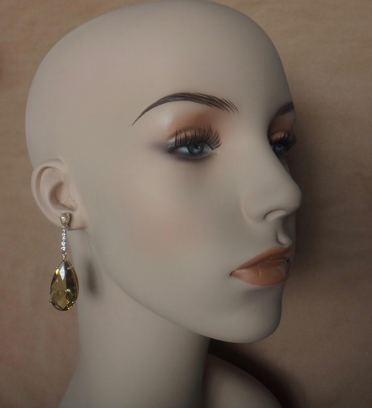 Perfectly matched pear shaped golden zircons (origin: Sri Lanka) begin the journey in these dangle earrings.  There are five graduated white diamonds set in white gold that lead to a beautifully cut and matched pair of lemon citrines with intense