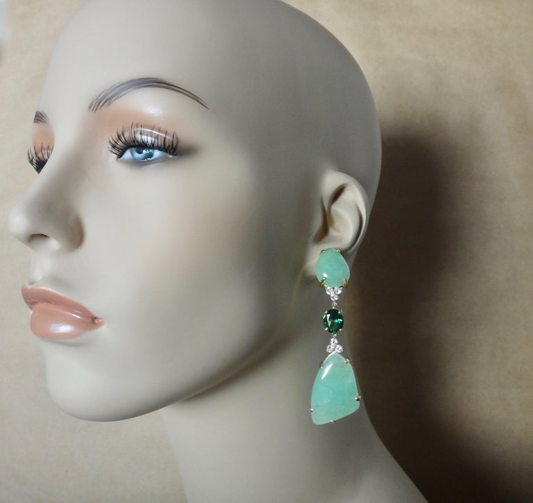 Free-form cabochons of green beryl (origin: Brazil) are perfectly book matched in these dramatic dangle earrings.  Beryl is a large family of gems.  Well known members include emerald and aquamarine.  Lesser known but equally beautiful members are