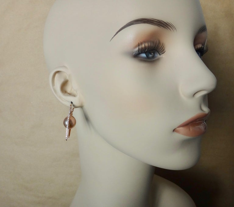 Pink Kasumi pearls (origin: Japan) are highlighted in these inventive Broken Hoop earrings.  The slightly baroque, extra large pearls are a deep shell pink color with tawny undertones and possess rich luster.  They are suspended within rose gold
