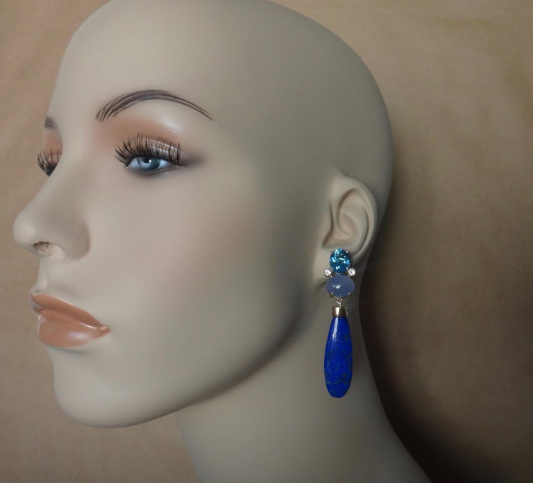 A palette of blues define these dramatic dangle earrings.  Oval cut, London blue topaz, brilliant cut white diamonds and cabochon blue chalcedony cluster together to form the tops.  Dangling below are are fantastic pair of Egyptian lapis lazuli.