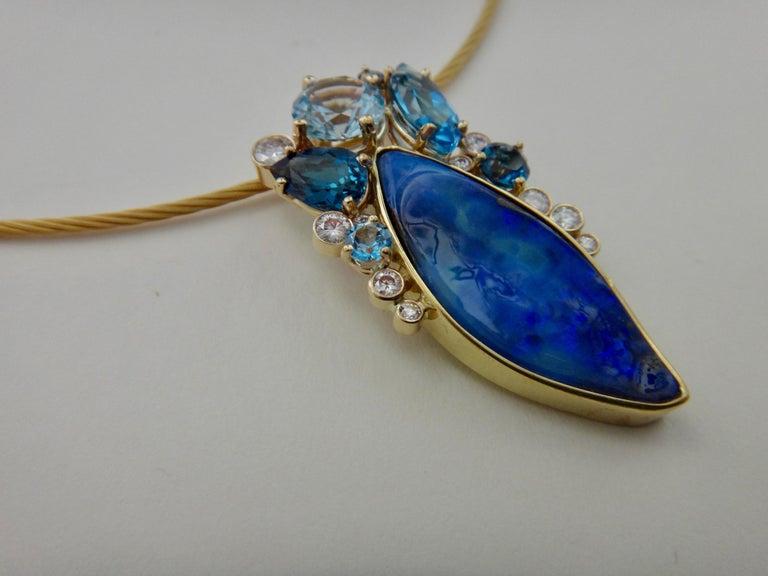 A boulder opal (origin: Queensland, Australia) is the centerpiece of this elegant