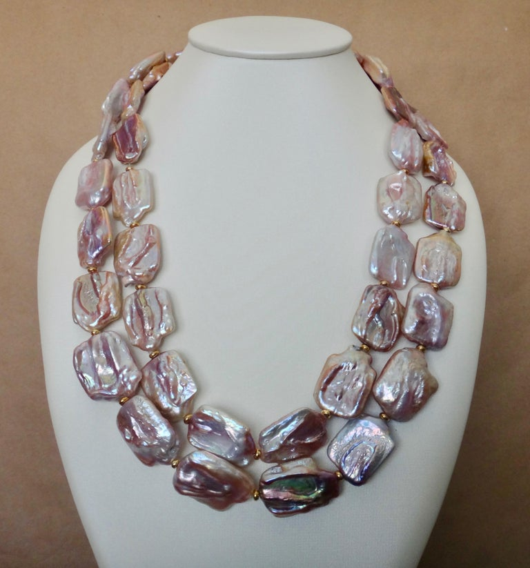 One long strand of pink tile pearls makes this a very versatile and easy to wear necklace.  The pearls average one inch by one inch in size.  They have a highly reflective, almost metallic luster and a dramatic range of colors from pale pink to