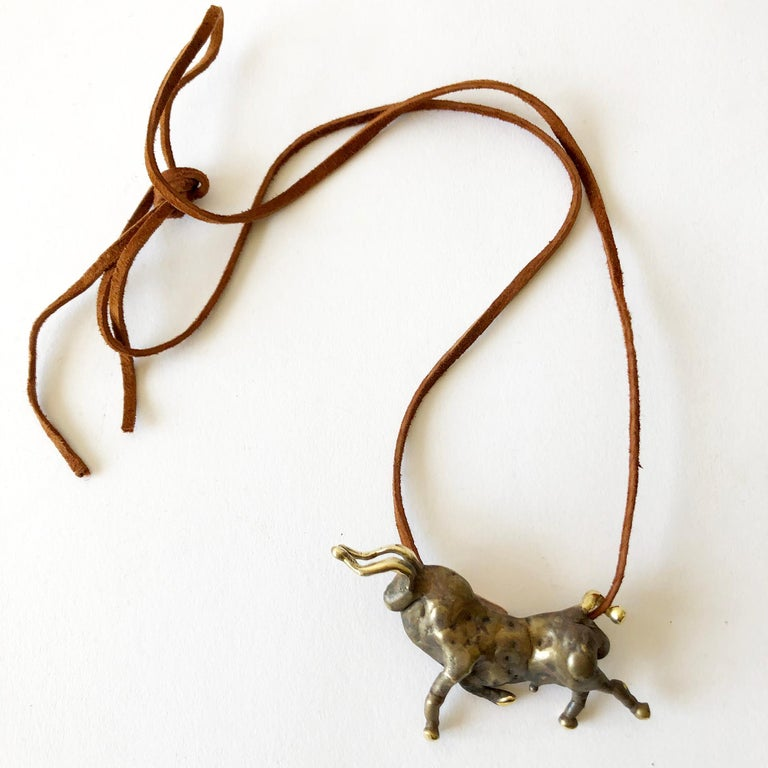 One of a kind, torch welded bronze bull pendant created by sculptor and jeweler Michael Schwade of West Fork, Arkansas.  In 1975, Schwade was a student of Ernesto Gonzalez, the master sculptor from Havana, and was taught his method of applying