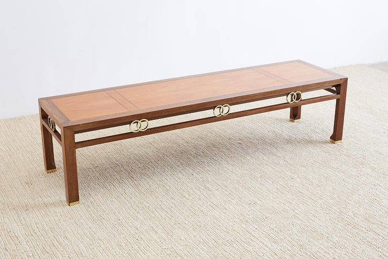 Distinctive Michael Taylor for Baker Furniture coffee or cocktail table from the Far East design collection. Constructed from walnut in a lighter shade finish on the segmented top and a darker finish on the frame. Decorative brass rings on each side