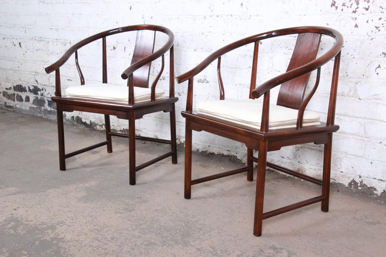 An exceptional pair of Hollywood Regency chinoiserie club chairs designed by Michael Taylor for his Far East collection for Baker Furniture. The chairs feature solid walnut frames with an Asian-inspired horseshoe design. The ivory upholstery with