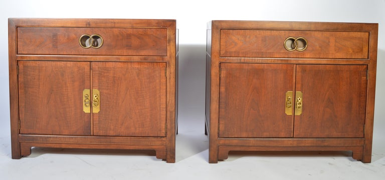 A pair of Baker nightstands designed by Michael Taylor for their Far East collection having brass pulls with signature behind each. Constructed with a blend of mahogany and walnut,