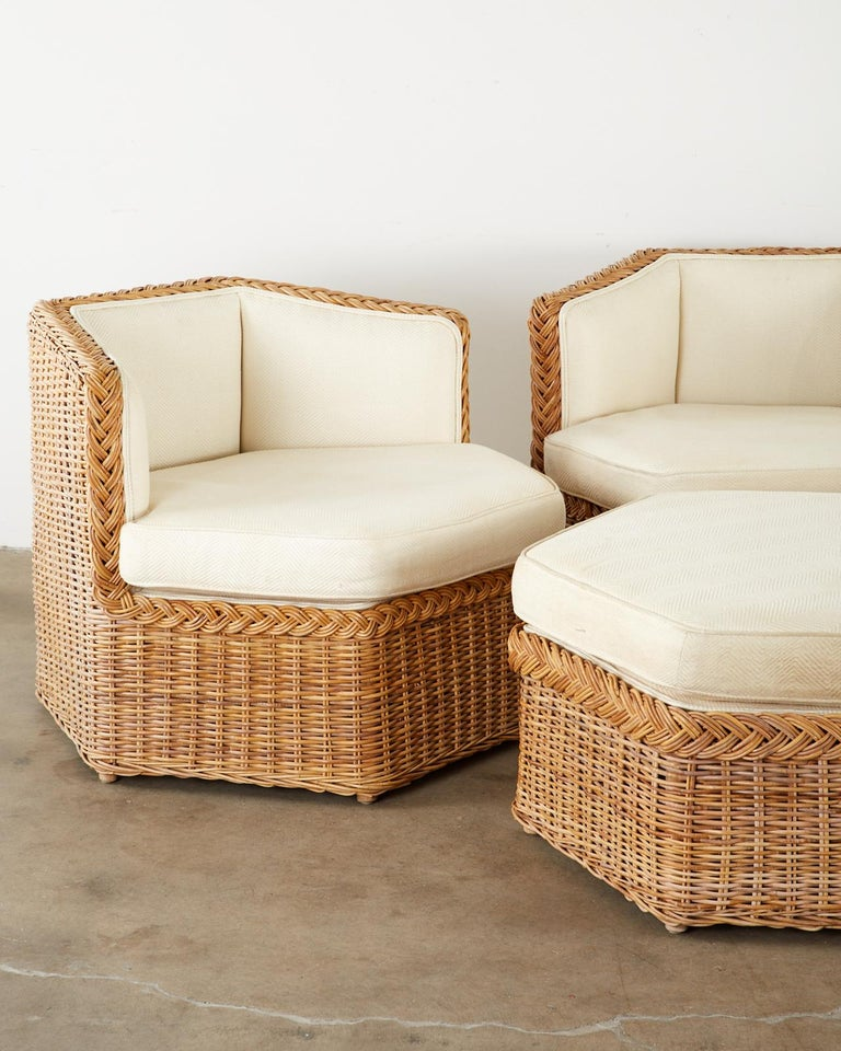 Stylish modular seating sofa set or suite consisting of three hexagonal shaped lounge chairs and a conforming ottoman. Handcrafted from woven rattan wicker in the manner and style of Michael Taylor. Topped with off-white thick cushions and padded