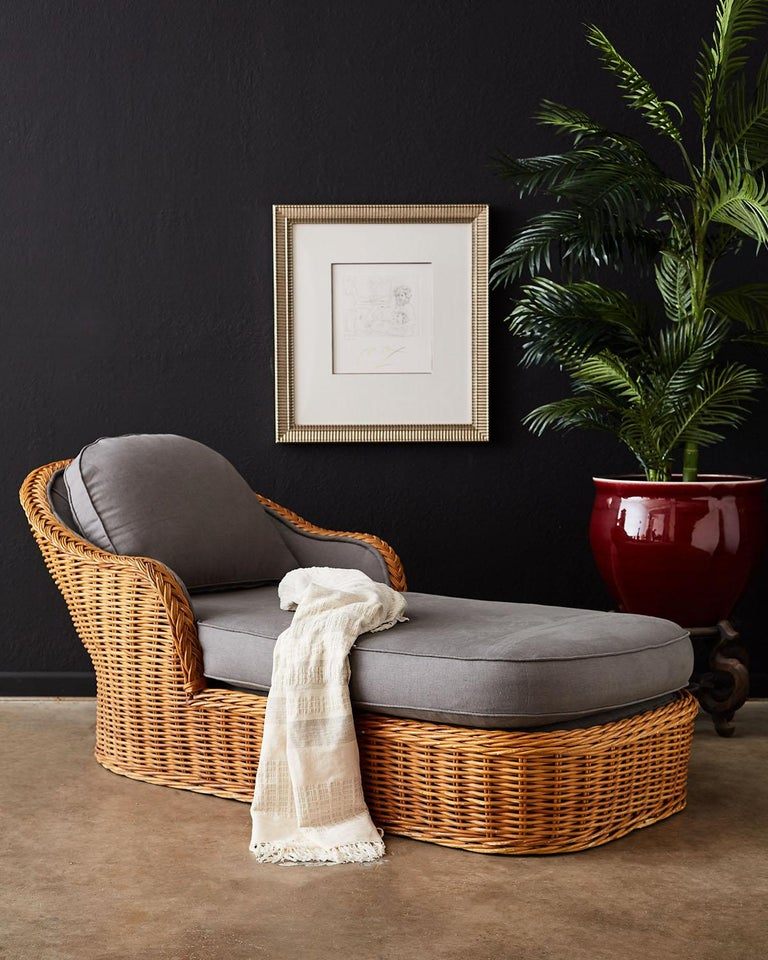 Oversized wicker and rattan chaise lounge or chaise longue made in the manner and style of Michael Taylor. Large rattan frame covered with woven stick wicker with a decorative braided arm crest. The generous seat has a thick cushion on top and a