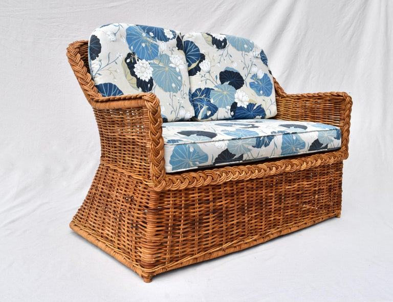 A striking Michael Taylor braided wicker rattan loveseat settee upholstered in new vintage stock Lotus flower cotton. Seat 18