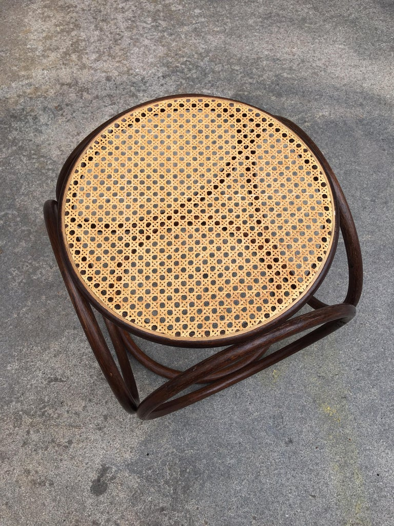 Classic Michael Thonet caned ottoman. Dark Walnut stained frame with light colored caning. Perfect to use as a side table or ottoman!