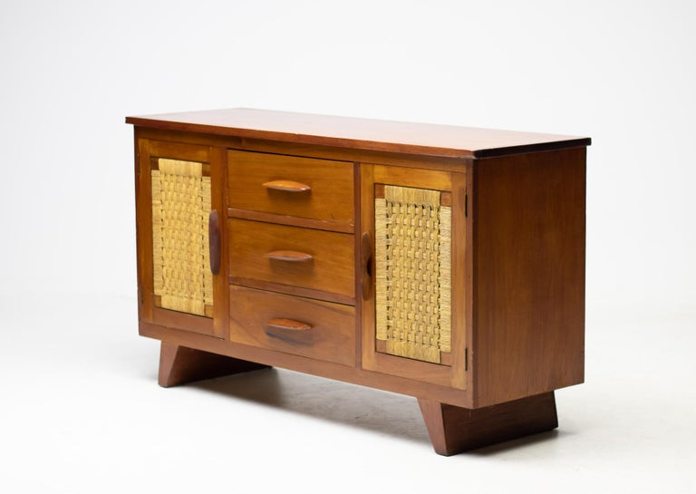 An important solid mahogany sideboard with doors on either side and 3 drawers at the centre.  The doors frame a beautiful basket weave of rattan cord.   Provenance: The office of the Mexican ambassador, Mexican embassy, The Hague, The