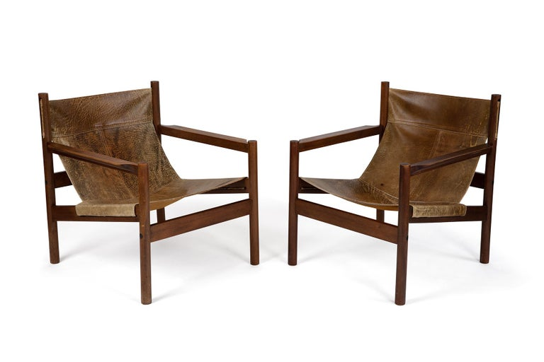 Rare Michel Arnoult wood and patinated leather sling style lounge chairs from Brazil. The leather on the back of one chair still sports the branding mark from the cowhide. Price listed is for the pair.
