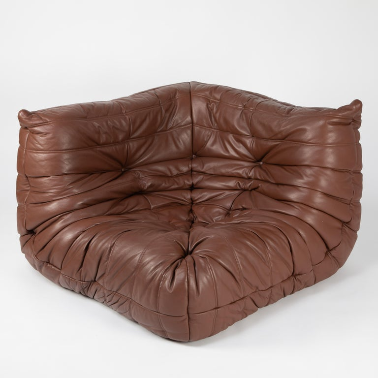 Extraordinarily comfortable classic corner chair from French designer Michel Ducaroy's Togo line for Ligne Roset. Designed in 1973, the Togo collection features ergonomic all-foam forms with quilted covers, this example in a lovely whiskey-color