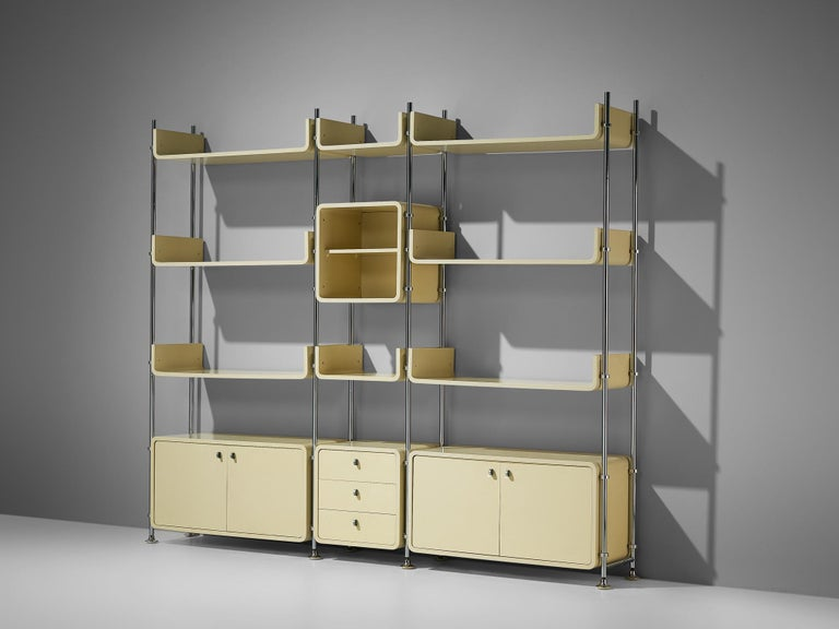 Michael Ducaroy, free-standing wall unit, steel, lacquered wood, France, 1970s  Michael Ducaroy designed this free-standing wall unit in the 1970s. In three columns are three closed cabinet, one open cabinet and eight shelves to find. The cream