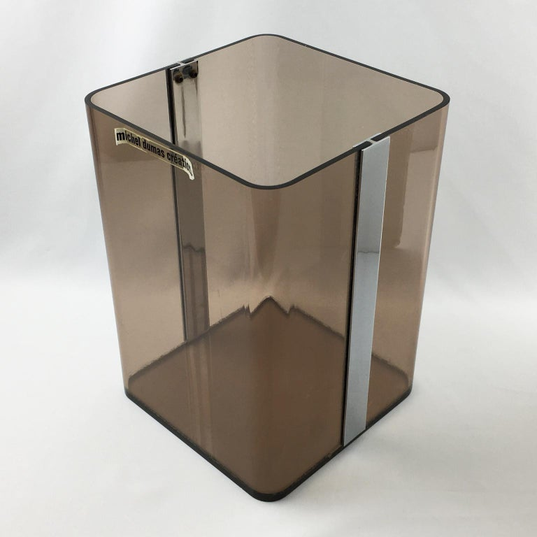 Elegant Lucite paper waste basket designed for Roche Bobois by Michel Dumas Creations in 1970s. Geometric tall shape with chrome accent and transparent gray smoke Lucite. Great accessory for any modern interior, office or bathroom. Still has its