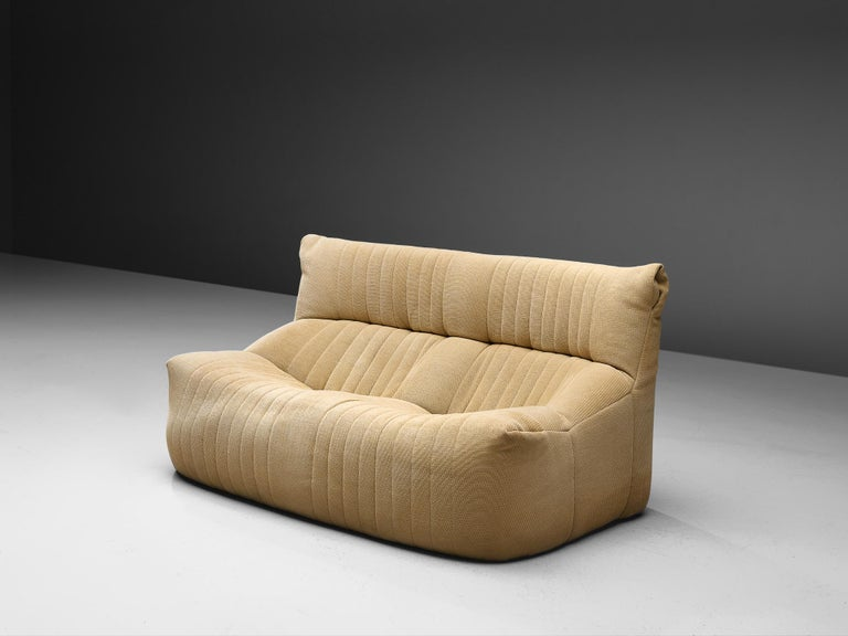 Ligne Roset, sofa, fabric, France, circa 1973.  This comfortable and grand two-seater sofa is manufacture by Ligne Roset. This model features a solid base with a rounded, bulky seat and a high back. The fabric is tufted with vertical lines. A highly