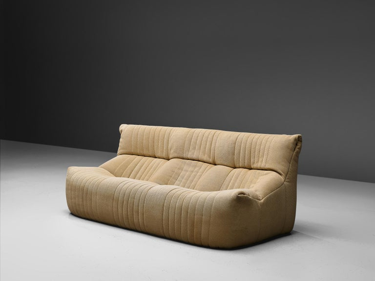 Ligne Roset, sofa, fabric, France, circa 1973.  This comfortable and grand three-seater sofa is manufactured by Ligne Roset. This model features a solid base with a rounded, bulky seat and a high back. The fabric is tufted with vertical lines. A