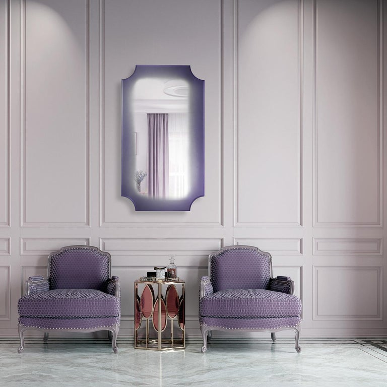 A modern and rectangular shaped mirror that features concave corners. The frame is made of wood with a riace bronze finish, however other finishes are available on request. The mirror, pictured here in purple, can be ordered in different colors.