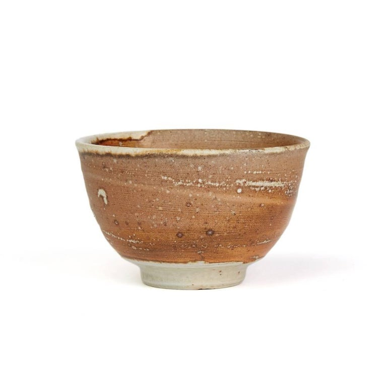 A fine vintage British studio pottery bowl by renowned potter Micki Schloessingk (b. 1949) and made in Swansea, Wales. The stoneware bowl is of rounded shape decorated in red and brown speckled slips with a matted finish over a stone ground standing