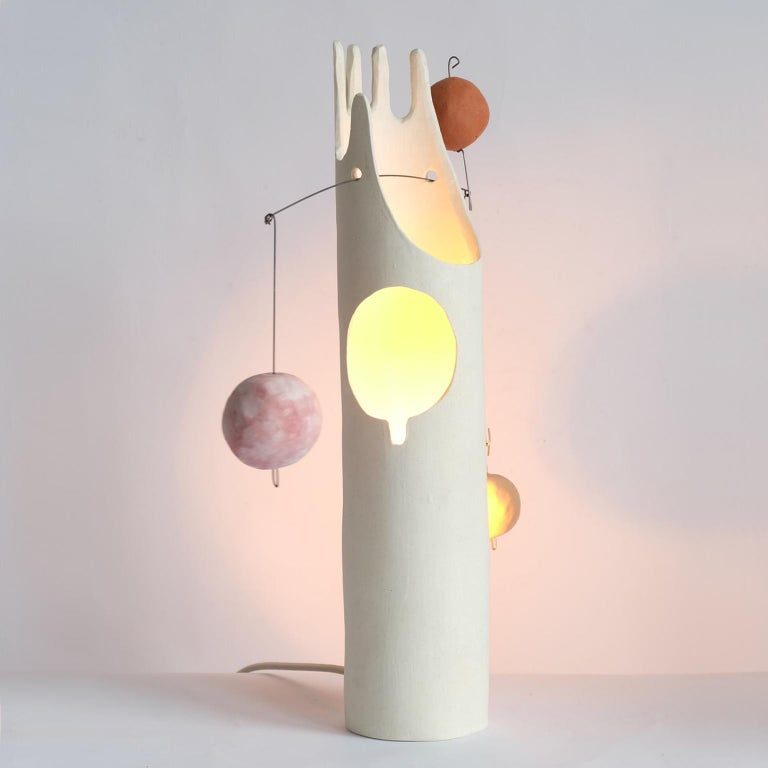 Nico's Cousin Mico is a contemporary hand-built sculptural ceramic table lamp that inspires the joy of working with hands through unpacking, assembling and balancing weights. The handmade ceramic globes and the hanging steel wire come fit right
