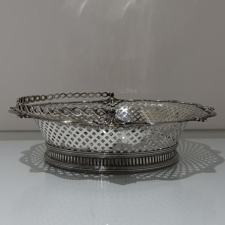A beautiful and unusual designed shaped oval swing handled cake basket decorated with hand pierced lattice work to the outer wall of the bowl and has a stunning applied alternate reed and fleur de leaf border for decorative highlights.