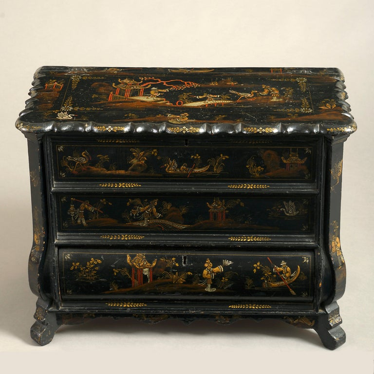 A charming mid-18th century black japanned work box, in the form of a miniature bombé commode, the overhanging shaped top and bottom drawer opening to reveal red painted compartments, decorated throughout with gilded chinoiserie.
