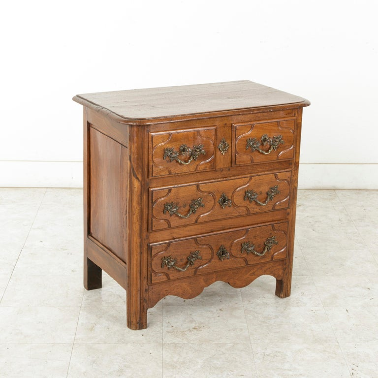 This mid-18th century French Louis XIV period hand carved chestnut commode or chest is from the Ile de France region surrounding Paris. Of an unusual small scale originally meant for a Paris apartment, this piece features four drawers of dovetail