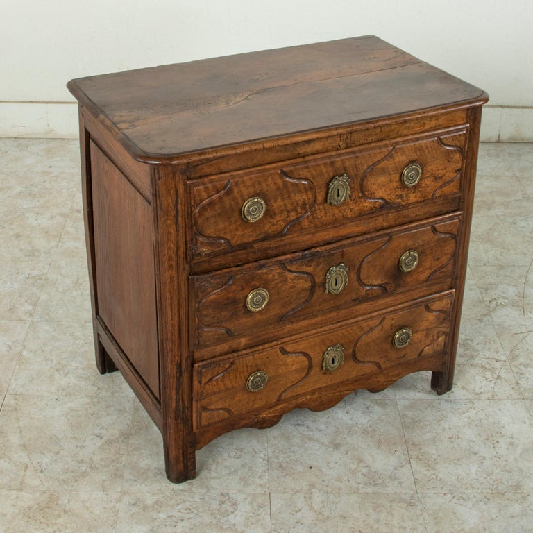 Of an unusual small scale, this 18th century French Louis XIV period commode or chest is constructed of solid hand carved walnut with paneled sides and beveled top. Originally created for a Paris apartment in the Ile de France region, this piece