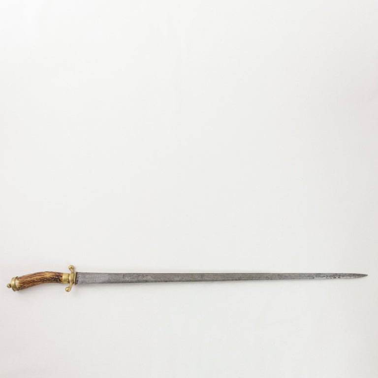 This mid-18th century French Louis XV period hunting short sword features a 26 inch long tapered steel blade engraved with a crown and star on each side indicating that this piece once belonged to a noble. An engraved hunting scene with a wild boar