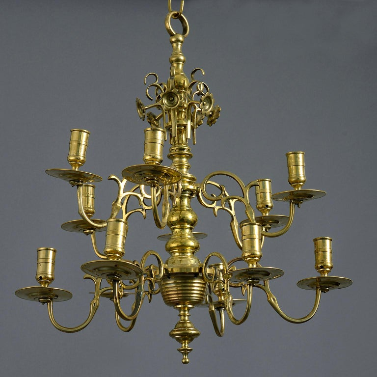 A mid 18th century George II brass chandelier the knopped centre issuing 12 scrolling branches over two tiers.