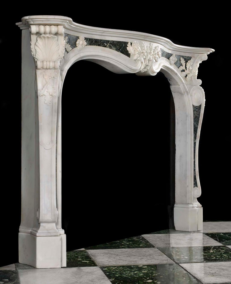 An important, rare mid-18th century Georgian English Rococo antique fireplace surround in Statuary and Maurin green marble influenced by the designs of Sir Henry Cheere (1703-1781) and Isaac Ware (1704-1766). The serpentine shelf rests above a