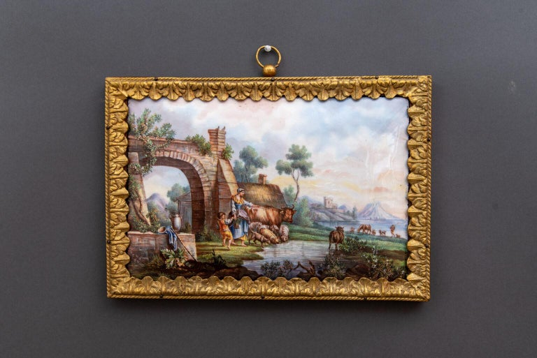 Rectangular porcelain plaque by Sevres with polychrome decoration of a majestic lake scene with figures and animals, a farm and the ruins of an arch on either side of a lake that extend in the distance to a castle and mountains. Gilt bronze frame,