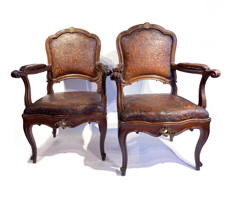 Pair of armchairs Original impressed leather covers Milan, circa 1750 They measure: 40.94