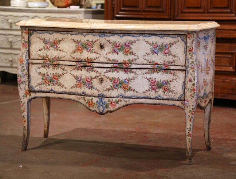 This elegant antique commode was crafted in Venice, Italy circa 1760, standing on four curved legs over a scalloped apron, the chest has two bombe drawers across the front decorated with hand painted floral motifs. The top is dressed with a