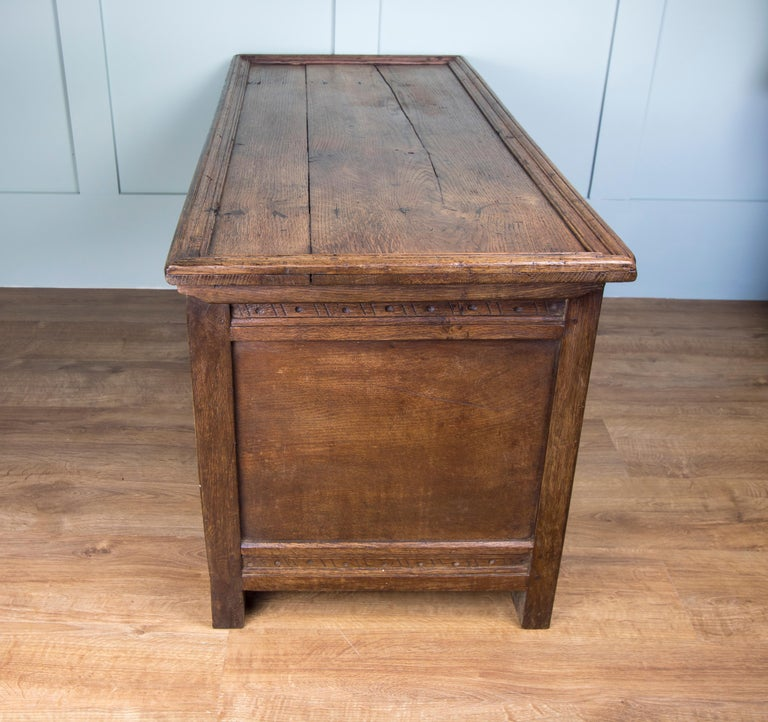 This sturdy oak joined coffer believed to date from the mid-18th century. Decorative carved front featuring three panels. Hinged three plank top with original ironmongery but no key. We are investigating having a key made for it, so please message
