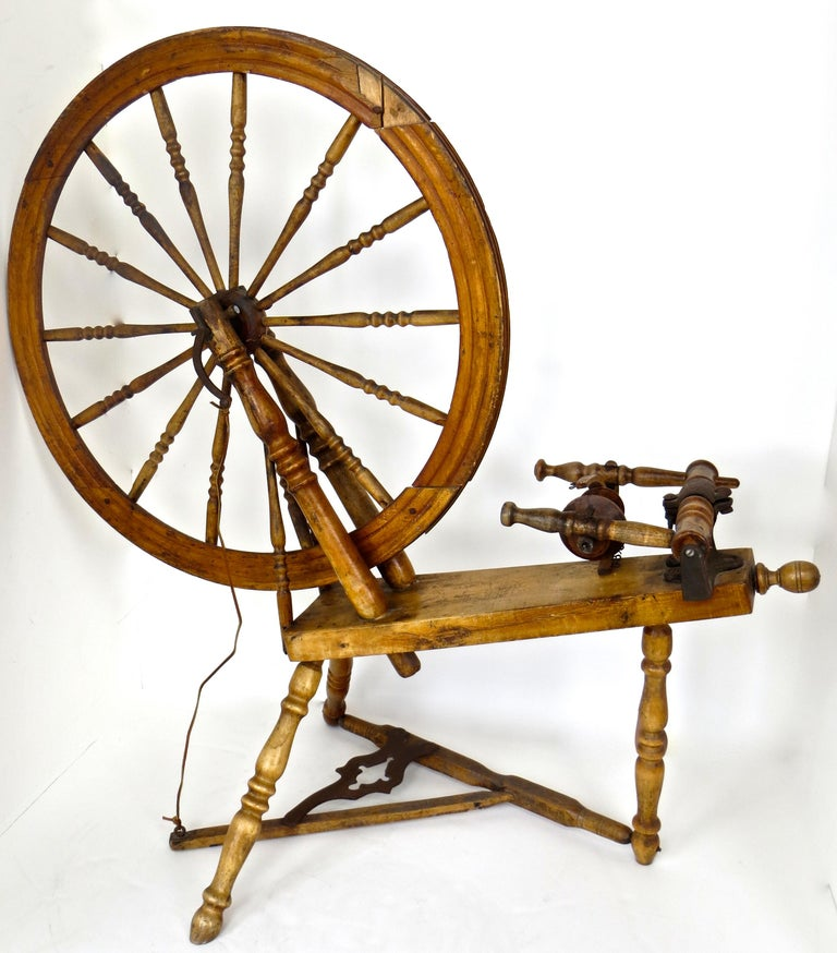 All original American spinning wheel, circa 1860, probably New England; with original flywheel and bobbin. The flywheel (drive wheel) consists of 14 original turned spindles; the treadle and bobbin