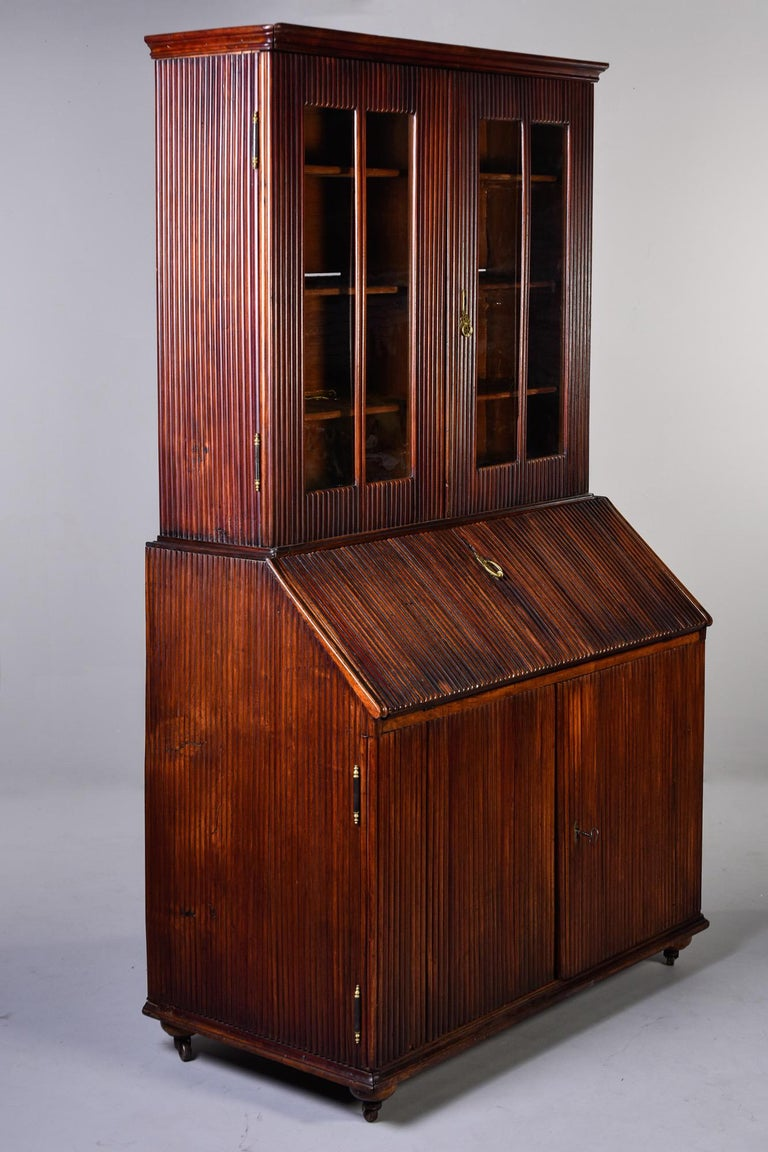 English cabinet features a reeded walnut base with fold down desk, internal shelves at the bottom, caster feet and glass-fronted book shelves on the top, circa 1850s. Unknown maker. Very good overall antique condition with crack on front of base and