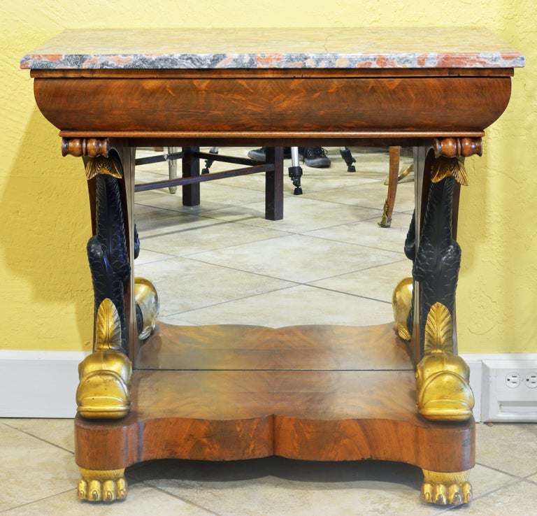 This great console table features a Siena marble top above a curved frieze fashioned as a drawer. It rests on two elaborately carved upswung dolphins with gilt heads and ebonized tails sitting with a mirrored back panel on the shaped base and gilt