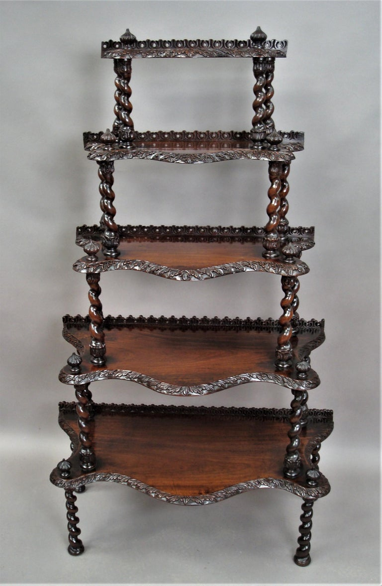 Unusual mid-19th century Anglo-Indian Padouk Whatnot; the five graduating tiers of exaggerated serpentine form, with well carved acanthus leaf molded edges and a pierced low gallery to the rear, all supported on barley twist columns with foliate